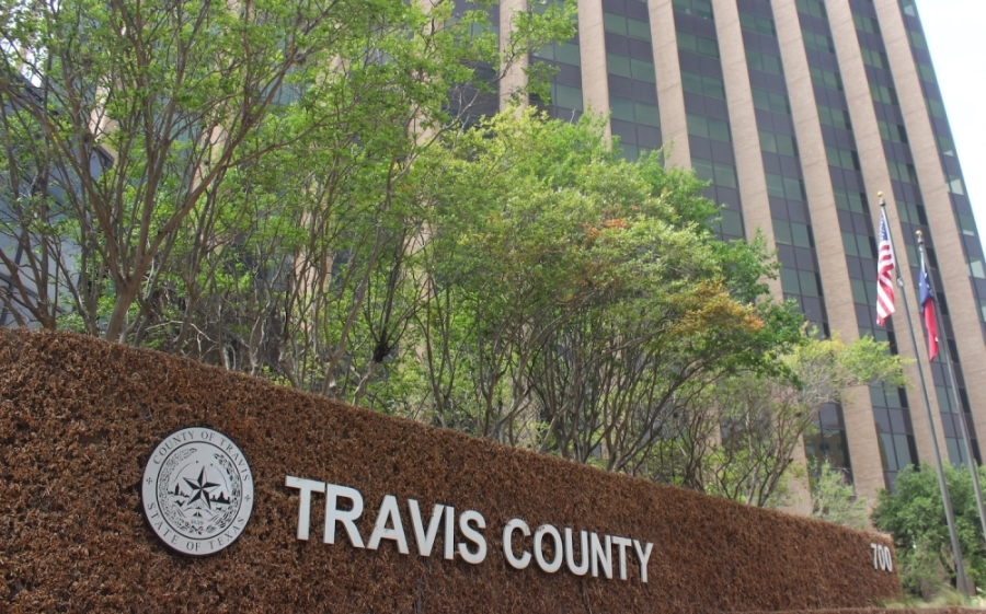 Photo of a sign thta says Travis County outside a building