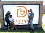 family poses by dogtopia sign