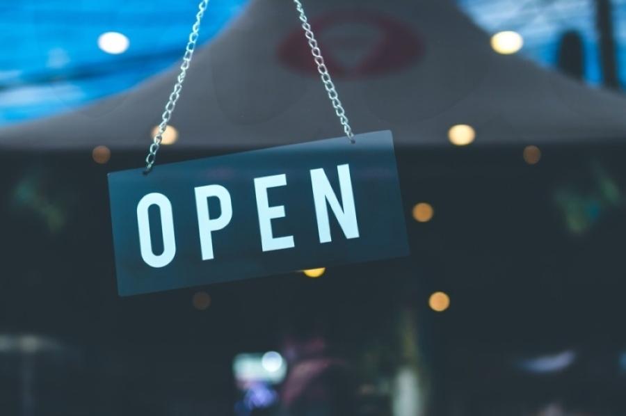 open sign hangs in business door