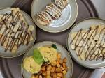 Plates of eggs, potatoes, and crepes