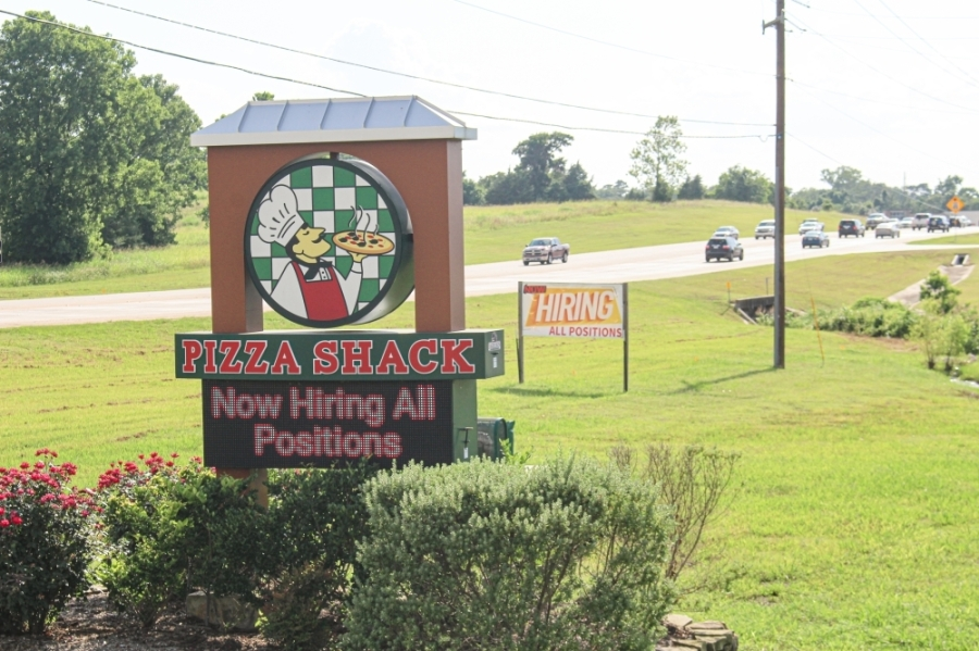 """Many restaurants along Hwy. 105 in Montgomery, such as Pizza Shack, have """"now hiring"""" signs displayed. (Eva Vigh/Community Impact Newspaper)"""