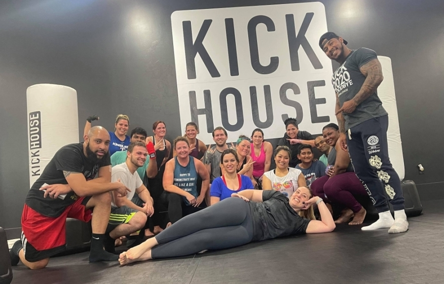 People posing in front of KickHouse decal in gym