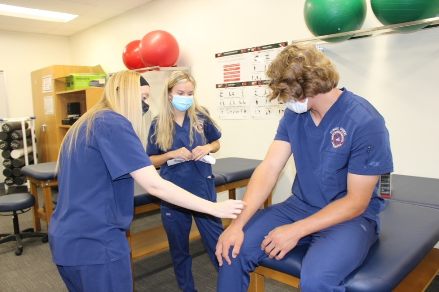 McKinney North High School CTE department chair Aly Deal (left) shows student Katie Gimlin how to apply kinesiology tape on fellow student Ethan Weslowki. (Miranda Jaimes/Community Impact Newspaper)