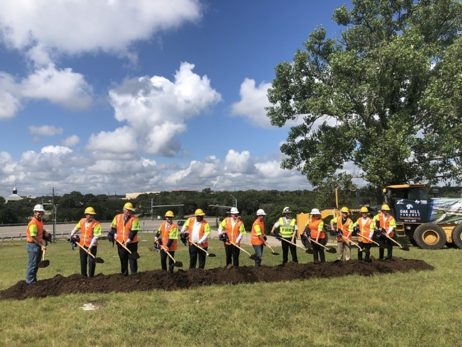 A group of officials breaks ground on the Oak Hill Parkway project. (Benton Graham/Community Impact Newspaper)