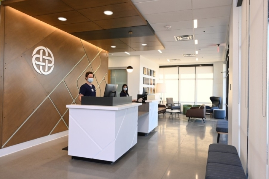 Urgent care clinic workers stand behind a front desk