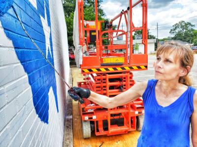 Beth Mankin Jones is painting the city's mural at the visitor and information center on West Main Street. (Courtesy Mike Baxter)