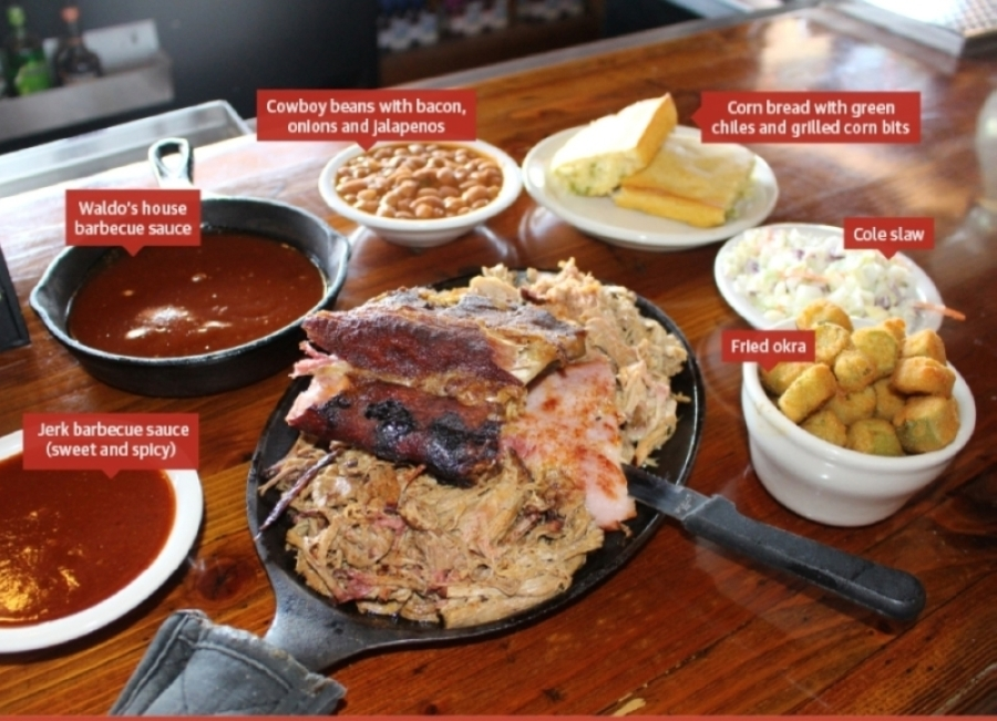 The Super Sampler ($23.99) comes with three choices of meats—shown are pulled beef, sliced ham and pulled pork—topped with a quarter-rack of baby back ribs. (Tom Blodgett/Community Impact Newspaper)