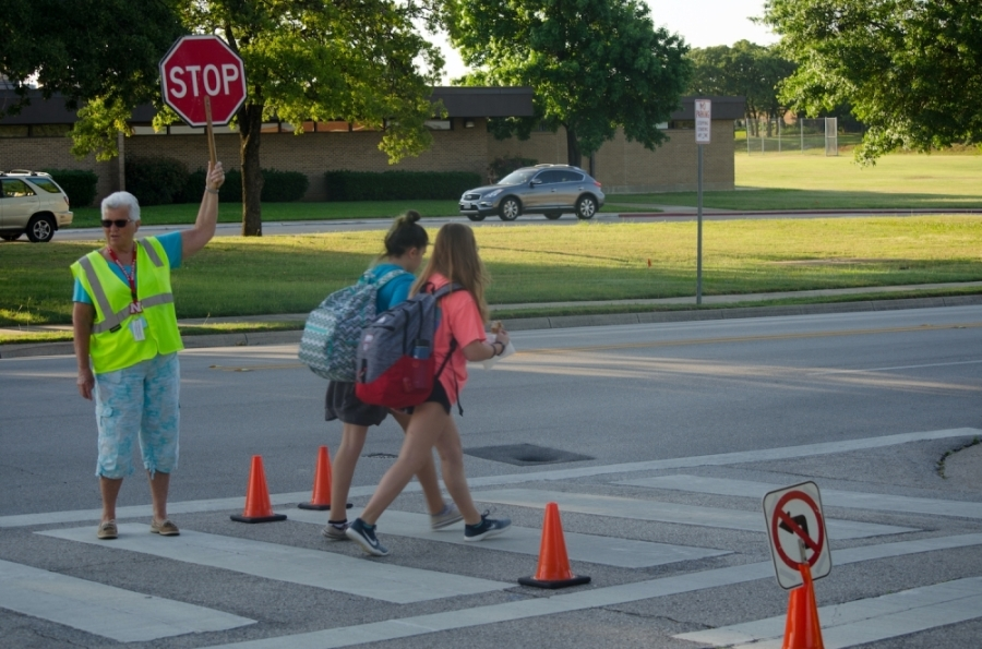 School crosswalk with crossing guard and two students
