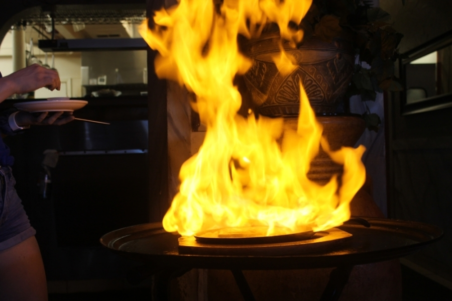 The flaming saganaki is lit up tableside for diners, and served with baked or fried pita. Gyro meat, chicken, shrimp and vegetables can also be added; the dish starts at $16. (Colleen Ferguson/Community Impact Newspaper)