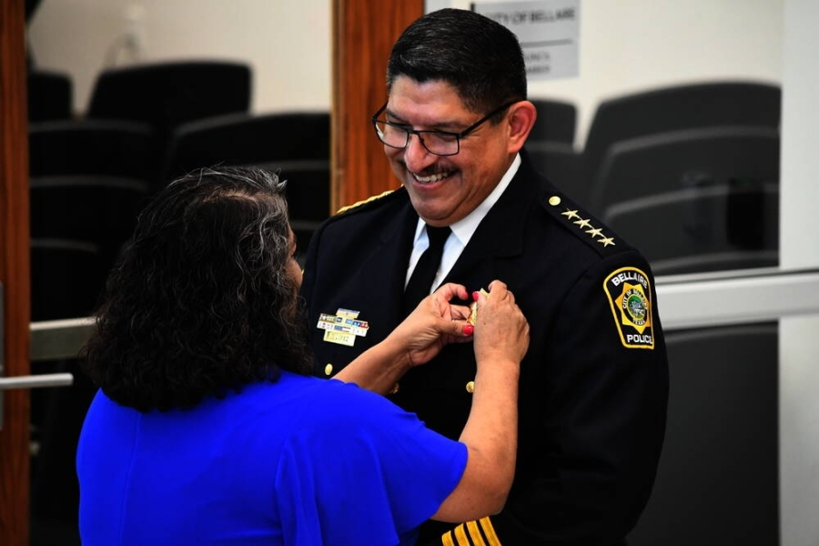 Onesimo Lopez officially receives his badge from his wife, Faby, to mark his promotion as Bellaire's new chief of police during an Aug. 2 swearing-in ceremony. (Hunter Marrow/Community Impact Newspaper)