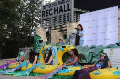 Mayor Jane Hughson speaking at the kick off event, surrounded by mermaids. (Zara Flores/Community Impact Newspaper).
