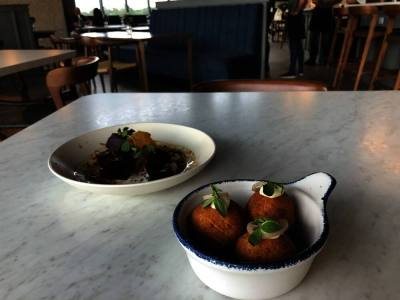 Le Vacher's most popular appetizer are fried dessert-like balls with Emmenthaler cheese, roasted garlic aioli and pickled shallot. (Community Impact Newspaper/Maggie Quinlan)