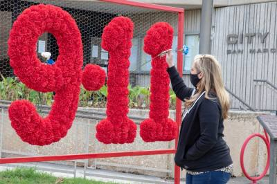 An attendee adds to a temporary flower memorial in front of San Marcos City Hall at the event commemorating 9/11 in 2020. (Photo courtesy City of San Marcos)