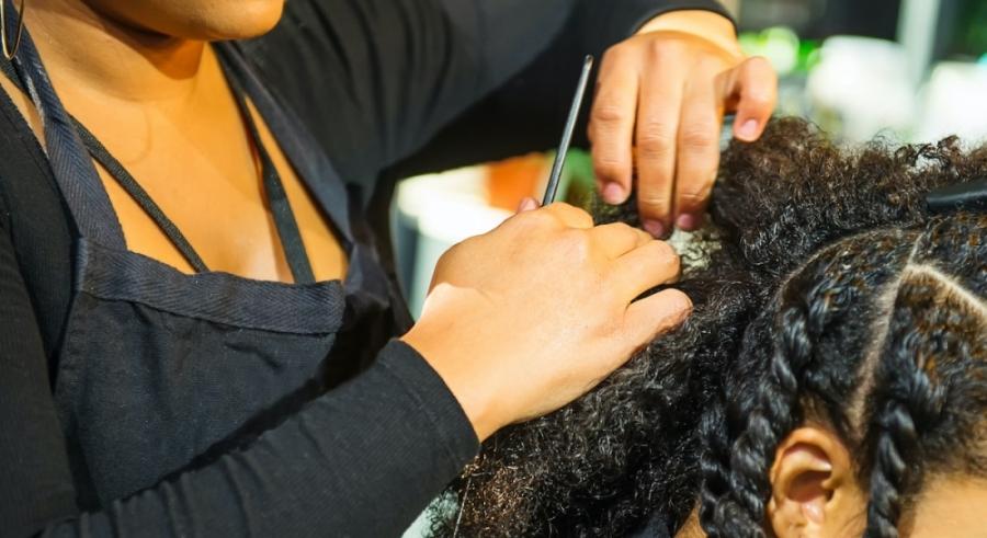 Woman braiding hair.