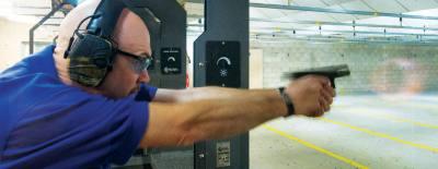 Hood demonstrates proper firearm grip and stance at Shady Oaks Gun Range in Cedar Park.