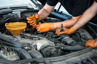 Two mechanics working on a vehicle in a garage or service workshop, close up of their gloved hands and equipment in the engine compartment