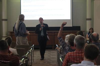 Sherwood Oaks resident David Swann (left) addresses Tyler Patrick, a principal with Sasaki Associates Inc., the architecture firm working on St. Edwardu2018s Universityu2018s master campus plan.