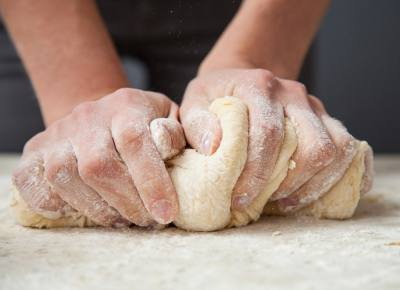 Woman's hands knead dough on a tablen