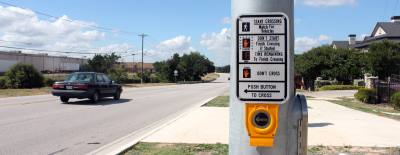 A pedestrian hybrid beacon allows a user to push the button and activate a signal that stops traffic so the person can safely cross a street.