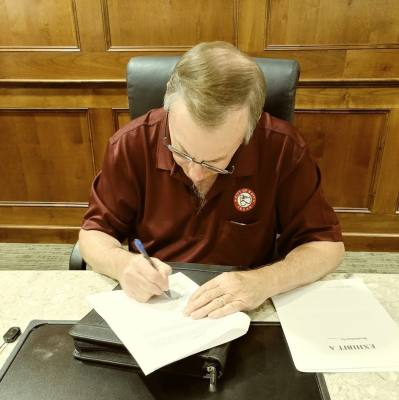 Katy's Mayor Chuck Brawner signs the contract with Costello, Inc. immediately after the special council session adjourned.