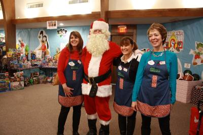GRACE Christmas Cottage helpers and Santa Claus take a photo.