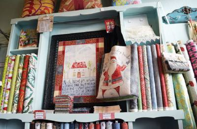 A colorful in-store display features holiday fabrics as well as project ideas that offer different uses for the fabrics.