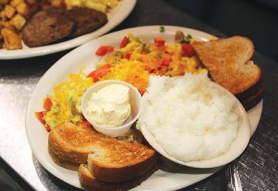 Eggs scrambled with green and red bell peppers, onions and mushrooms are served with sides.