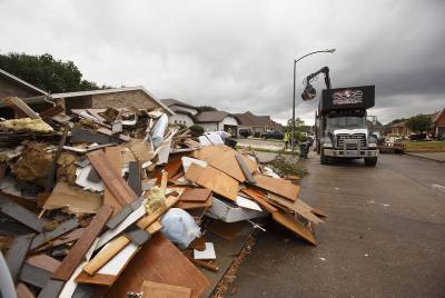 Debris from Harvey flooding is removed from a Port Arthur neighborhood on Wednesday, Sept. 20, 2017.
