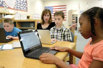 Students at Naumann Elementary School work with school librarian Karen Jordan.