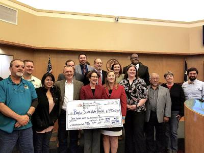 Buda City Council, staff and the Buda Economic Development Corps. stand with sign check to Baylor Scott & White.