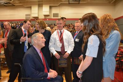 Gov. Greg Abbott speaks with a student from Briarhill Middle School.