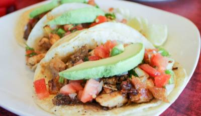 La Cocinau2019s street tacos come with chopped beef or chicken fajita meat with onions in a corn tortilla. The tacos are topped with fresh pico de gallo, avocado and lime.