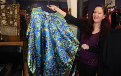 A mumu, displayed here by owner Adriana Martinez, is among the unique items found at the South Austin vintage boutique.