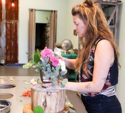 Alex Zody, lead designer, prepares a flower arrangement for a customer. n