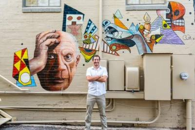 The portion of artist Buddy Pajak's mural found on the side of the New Braunfels Art League building portrays a portrait of Pablo Picasso and incorporates elements of his artistic style.