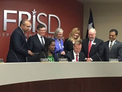 FBISD trustees gather as board President Jason Burdine signs the approval for the 2018 bond election.