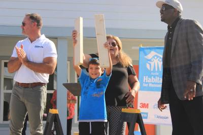 Jairdan Arriaga gestures for the crowd after a board cutting ceremony celebrating the opening of four homes in East Austin on Saturday, July 28. Habitat for Humanity and the Guadalupe Neighborhood Development Corporation donated the homes to families, including Arriaga and his mother, Rachel Seca.