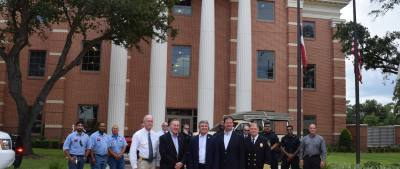 U.S. Rep. Michael McCaul (front, center) poses with city officials at a photo opportunity after the press conference. In the background, flags fly at half-staff in honor of U.S. Sen. John McCain, R-Arizona, who died over the weekend.