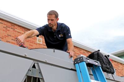 A Frisco ISD maintenance employee works on the air system at Christie Elementary School.