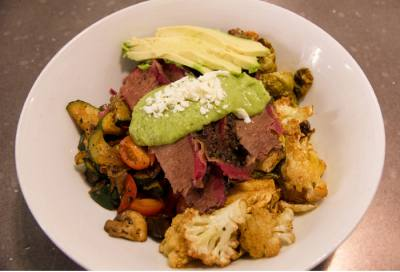 A brisket bowl comes with cauliflower, mushrooms, mixed veggies, avocados, tomatoes, Brussels sprouts and an avocado verde sauce.