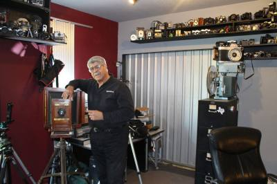 Vic Cherubini, president and founder of Epic Software Group and the Epic Creative Co-op, stands alongside a portion of his camera collection.