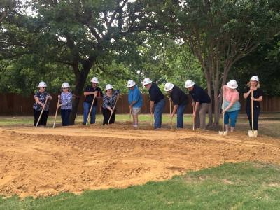 Town officials and friends of the library break ground on the expansion.
