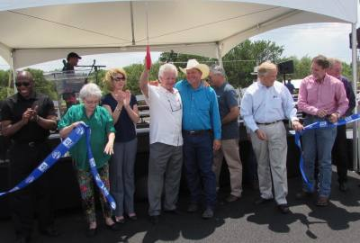 Travis County Commissioner Gerald Daugherty holds scissors up in celebration with Hays County Commissioner Mark Jones at the May 25 ribbon cutting for SH 45 SW.