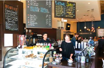 Katy Bounds, forefront, general manager of all Lola Savannah Coffee Lounge and Grove Wine Bar & Kitchen locations, and barista Niki Brown, left, work behind the counter in Westlake.