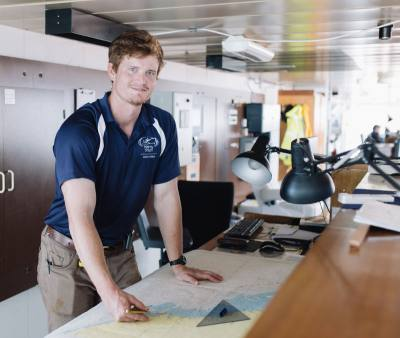 Coltan Coleman, League City resident and Mercy Ships volunteer, studies charts aboard the Africa Mercy in Guinea, West Africa.