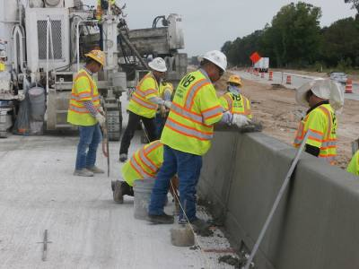Crews working on Hwy. 290 smooth out freshly-poured concrete on a railing for the widened outbound mainlanes near Mason Road in Cypress.