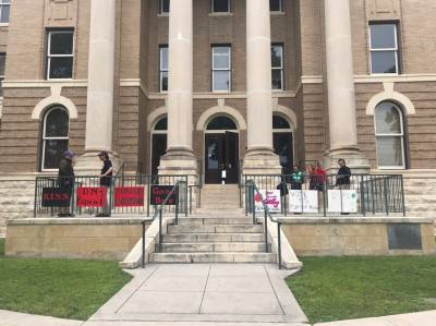 Hays County residents gather outside the courthouse May 10 to show their support for the submission of a grant to create a public defender's office. n