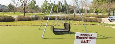 Wheelchair swings are one example of equipment used on inclusive playgrounds.