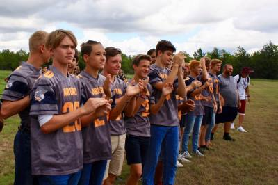 Aristoi Classical Academy football players cheer as the headmaster cuts the ribbon for a new athletic field. n