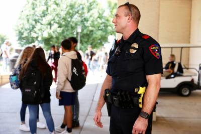 School Resource Officer Troy Bourgeois watches over students during a passing period at Plano East Senior High School. Bourgeois is one of 25 current SROs from Plano Police Department.